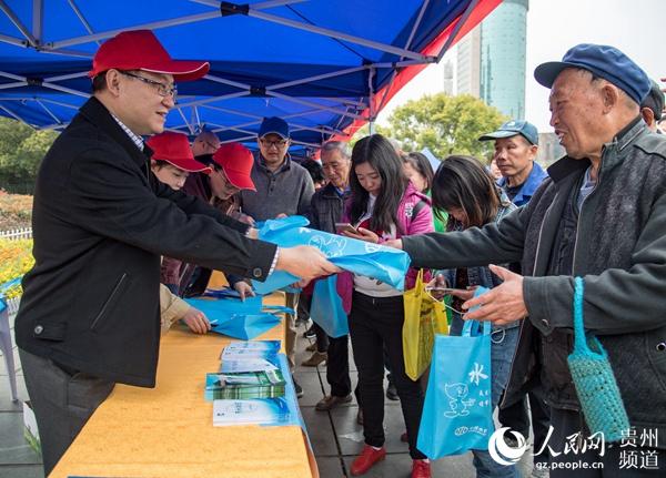 万博手机省水利厅党组副书记、副厅长帅文在贵阳市人民广场活动现场发送宣传材料。(杨良强 摄)